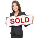 Realtor / Real estate agent sold sign. Real estate agent holding sold sign isolated on white background. Beautiful cheerful Asian / Caucasian female realtor royalty free stock images