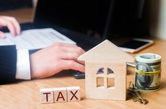 The realtor`s hand holds a bundle of money near the house with the keys. Concept of real estate tax. Payment of taxes on real est stock images