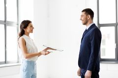 Realtor showing contract document to customer. Real estate business, sale and people concept - female realtor with clipboard showing contract document to Royalty Free Stock Photos