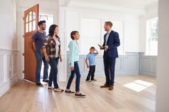 Realtor Showing Hispanic Family Around New Home Stock Image