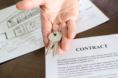 Realtor showing house keys. Over a contract Stock Photo