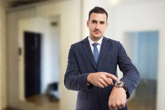 Realtor showing wristwatch as late for appointment gesture concept. stock image
