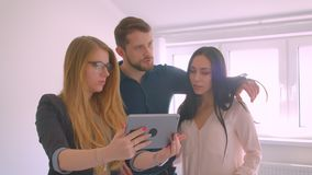 Realtor showing young caucasian couple the apartment for sale demonstrating and discussing the opportunities using. Tablet stock video