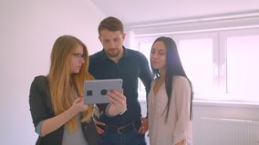 Realtor showing young caucasian couple the apartment for sale demonstrating the opportunities on tablet. Realtor showing young caucasian couple the apartment stock video