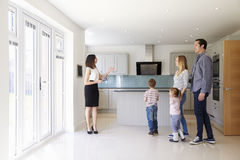 Free Realtor Showing Young Family Around Property For Sale Royalty Free Stock Photography - 79801737