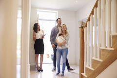 Realtor Showing Young Family Around Property For Sale Stock Photo