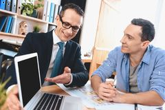 Realtor sitting at desk in office. Realtor is presenting laptop to father, mother and son. stock photos