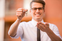 Realtor. Successful realtor in white shirt showing keys and smiling at camera Stock Image