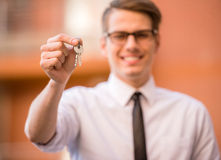Realtor. Successful realtor in white shirt showing keys and smiling at camera Stock Photos