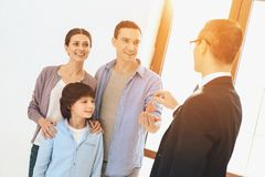 Realtor is giving keys to family in new apartment with cardboard boxes. stock image