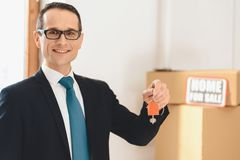 Realtor holding keys with house icon in new apartment with cardboard boxes. stock photos