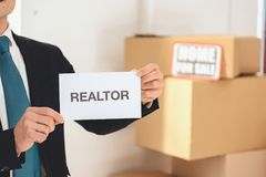 Realtor holding realtor sign in new apartment with cardboard boxes. stock images