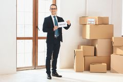 Realtor holding realtor sign in new apartment with cardboard boxes. royalty free stock image