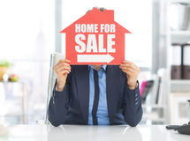 Realtor woman holding home for sale sign. In front of face Stock Photos