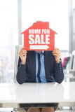 Realtor woman holding home for sale sign Stock Images