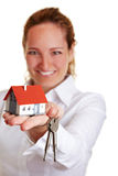 Realtor woman offering house keys. And small house Stock Photography