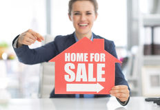 Realtor woman pointing on home for sale sign Stock Photo