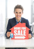 Realtor woman showing keys and home for sale sign Royalty Free Stock Photos