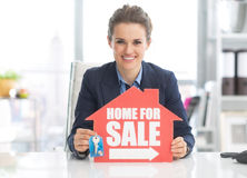 Realtor woman showing keys and home for sale sign Royalty Free Stock Photo
