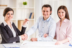 Realtor. Young couple signing financial contract with female realtor Royalty Free Stock Photos