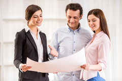 Realtor. Young couple with realtor are watching the plan of a house Royalty Free Stock Photo