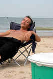Realxing. Man relaxing sitting on the beach stock photo