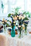 Сream and blue flowers in vases on a table with a lace table. Cloth. Wedding decorations Stock Images