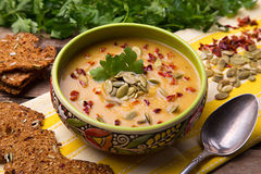 Сream soup from squash with thyme, paprika, pumpkin seeds, parsley and with rye crackers Royalty Free Stock Image