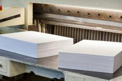Reams of cut paper pages on a cutter machine. Reams of neatly stacked cut white paper pages on a cutter machine in a print shop in a close up view Stock Photos