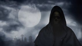 Reaper Figure Graveyard Full Moon 4K Loop. Features a hooded figure with skull face and a full moon with moving clouds in the background and birds circling over stock video