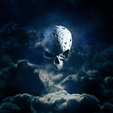Reaper moon rising. 3D render of cratered skull moon in night sky Royalty Free Stock Photo