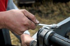 Reapiring Erntemaschine des Mannes Hand Stockfotografie