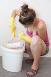 Reapplying Paint. Women reapplies paint on a paint roller while painting her room Stock Photos