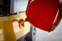 Reaprovisionamiento de combustible usando un tanque del galón para una carretilla elevadora o una máquina fotografía de archivo libre de regalías