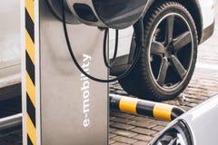 Reaprovisionamiento del automóvil para la e-movilidad en el coche del fondo, rueda de los coches eléctricos Foto de archivo libre de regalías