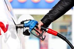 Reaprovisione el coche de combustible con gasolina imagenes de archivo