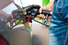 Reaprovisione el coche de combustible en una gasolinera Imagen de archivo