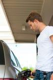 Reaprovisione el coche de combustible en una gasolinera Imagenes de archivo
