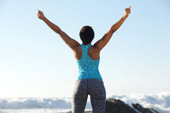 Rear of african american sports woman stretching arms by the sea Royalty Free Stock Images