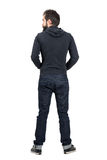Rear back view of bearded man in black hooded sweatshirt looking away. Stock Photography