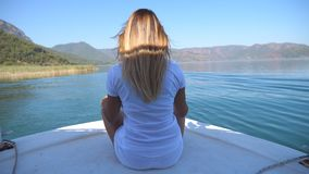 Rear back view of young girl sitting on bow of boat and looking to beautiful nature landscape on sunny day. Happy woman. With blonde hair enjoying summer travel stock footage
