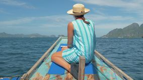 Rear back view of young girl sitting on bow of boat and looking to beautiful nature landscape during trip. Happy woman. 4K slow motion rear back view of young stock video