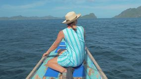 Rear back view of young girl sitting on bow of boat and looking to beautiful nature landscape during trip. Happy woman. 4K slow motion rear back view of young stock video footage