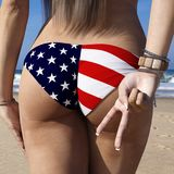 Rear backside view of a fit brunette female wearing an American flag style bathing suit at a sunny beach. Royalty Free Stock Images