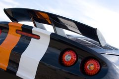 Rear of black racing car. With orange and white stripes Royalty Free Stock Photography
