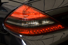 Rear brakelight. On shiny black performance car royalty free stock images