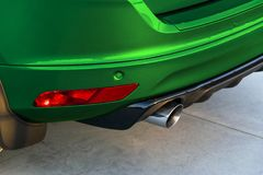 Rear bumper of a green car with exhaust pipe, modern car exterior details. Rear bumper of a green car with exhaust pipe, modern car exterior details Royalty Free Stock Photos