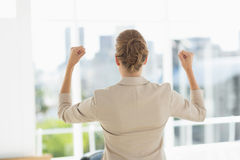 Rear of a businesswoman clenching fists in office Stock Photo