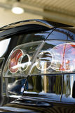 Rear end of car in showroom. With reflection on polished auto royalty free stock photo