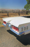 Rear-end 1960 Ford Thunderbird Convertible. The rear-end of a Classic 1960 shiny white Ford Thunderbird Convertible sitting in the sunshine on a country road by royalty free stock photo